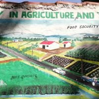 Mural of a person spraying a field next to the words 'food security' and 'pest control'